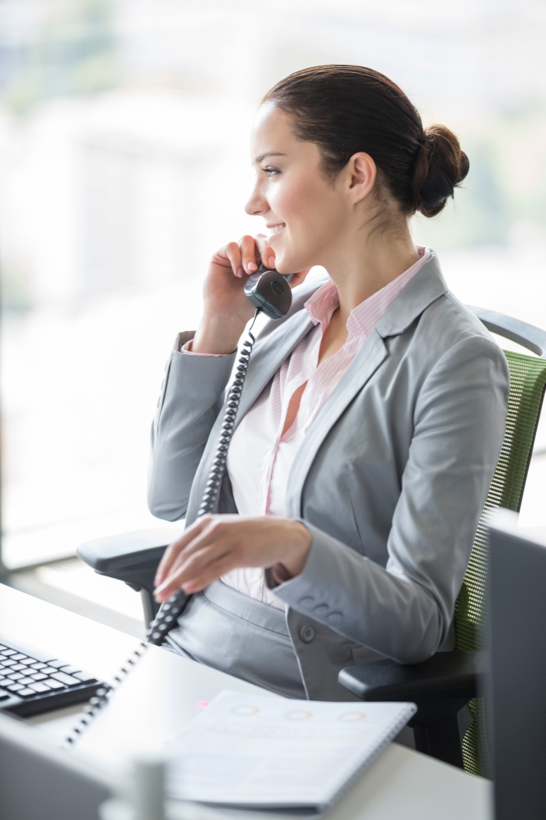 Smiling young businesswoman talking on landline phone in office